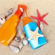 Stock Photo: Sunblock in bottles, shells and starfish on sand