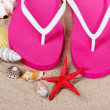 Beach shoes, shells and starfish on sand — Stock Photo