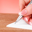 Pen in hand writing on paper — Stock Photo