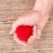 Red heart in hands on wooden background — Stock Photo #6796481