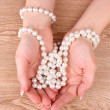 Royalty-Free Stock Photo: Woman hand with pearls on wooden background