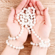 Woman hand with pearls on wooden background — Stock Photo #6796490