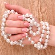 Woman hand with pearls on wooden background - Stock Photo