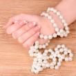 Woman hand with pearls on wooden background — Stock Photo