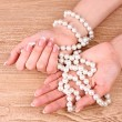 Woman hand with pearls on wooden background — Stock Photo #6796497