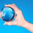 Crystal ball on hand. blue background — Stock Photo #6796531