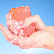Stock Photo: Hands with soap on blue background