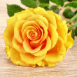 Yellow flower on wooden table - Stock Photo
