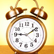 Old alarm-clock on yellow background — Stock Photo