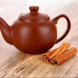 Cinnamon bark and teapot on wooden table — Stock Photo