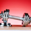 Dumbbell on red background — Stock Photo #6798438