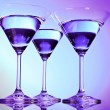 Three martini glasses on purple background — Stock Photo