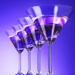 Four martini glasses on blue background — Stock Photo #6798655