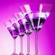 Four martini glasses on purple background — Stock Photo