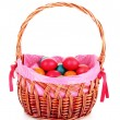 Wicker basket with Easter eggs isolated on white - Foto Stock