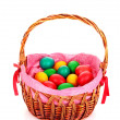 Wicker basket with Easter eggs isolated on white — Stock Photo