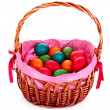 Wicker basket with Easter eggs isolated on white - Stock Photo