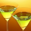Stock Photo: Glass with a green alcoholic beverage to a yellow-brown backgrou
