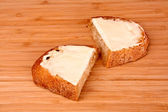 Slice of bread buttered on a wooden stand — Stock Photo