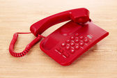 Red phone on wooden table — Stock Photo