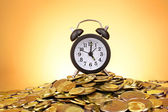 Alarm clock and coins on yellow background — Stock Photo