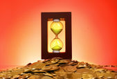 Hourglass and coins on red background — Stock Photo