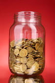 Coins in money jar on red background — Stock Photo