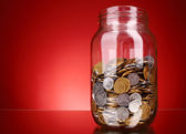 Coins in money jar on red background. Ukrainian coins — Стоковое фото