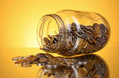 Coins spilling from a money jar on yellow background — Stock Photo