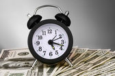 Alarm clock and dollars on gray background — Stock Photo