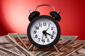Alarm clock and dollars on red background — Stock Photo