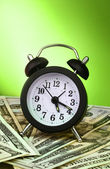 Alarm clock and dollars on green background — Stock Photo