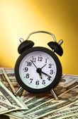 Alarm clock and dollars on yellow background — Stock Photo