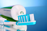 Toothpaste and brush on a blue background — Stock Photo