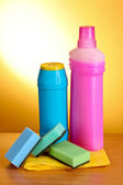 Assorted cleaning products on yellow background — Photo