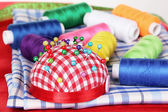 Bright thread, measuring tape and fabric — Stock Photo