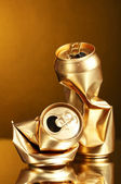 Crumpled golden tin can on a yellow background — Stock Photo