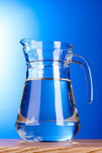 Water pitcher on blue background — Stock Photo