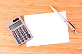 Pen, a sheet of paper and a calculator on a wooden table — Stock Photo