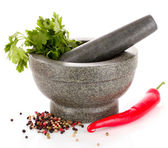 Mortar and pestle, parsley and pepper isolated on white — Stock Photo