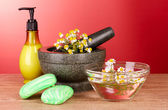 Mortar and pestle with soap and flowers on red background — Stock Photo