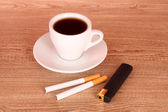 Cigarettes and cup of coffee on wooden background — Stock Photo