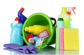 Detergent bottles, brushes, gloves and sponges in bucket — Stock Photo