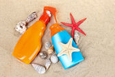 Sunblock in bottles, shells and starfish on sand — Stock Photo