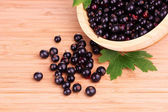 Fresh blackcurrant in bowl on wooden surface — Stock Photo