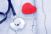 Stethoscope on ECG and red heart — Stock Photo