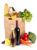 Vegetables in paper bag and wine bottles isolated on white — Stock Photo