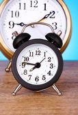Two clocks with different time on blue background — Stock Photo