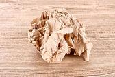 Bruin verfrommeld papier bal op houten textuur — Stockfoto