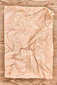 Bruin verfrommeld papier op houten textuur — Stockfoto